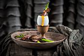 Gekochtes Ei in Eierbecher serviert mit Spargelstange im Speckmantel