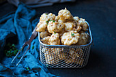 Deep-fried cauliflower in beer batter in a frying basket (vegan)