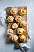Vegan yeast spirals dusted with icing sugar on a wooden board (seen from above)