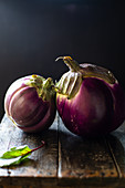 Two round eggplants on a wooden table