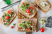Broccoli paste with feta cheese, olives and tomatoes on toasted bread slices