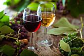 Zwei Gläser Rot- und Weisswein und Weintrauben