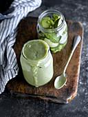 Ein Glas mit Smoothie-Zutaten und ein fertig gemixter grüner Smoothie