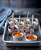 Metal tray with cups filled with various fruit ice pops on table