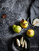 Birnen, ganz und in Spalten geschnitten auf grauem Untergrund (Aufsicht)