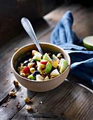 Porridge mit Äpfeln, Cranberries und Haselnüssen im Schälchen