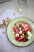 Watermelon and raspberry salad with feta cheese and pistachio nuts