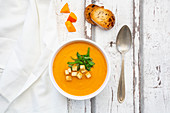 Pumpkin soup with croutons and basil