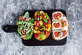 Slices of bread topped with figs, tomatoes, Parma ham and rocket