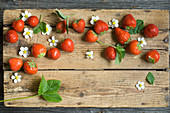 strawberries with leaves and flowers on a wooden board