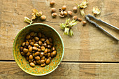 Freshly harvested hazelnuts in a bowl and next to it