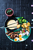 Cheesy fondue with sausages and vegetable
