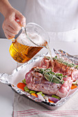 Light beer being added to ready-to-cook pork knuckle