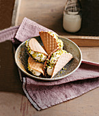 Wafer sandwiches with chocolate glaze, ricotta and orange cream and pistachio nuts