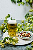 A mug of light beer with nuts and hops