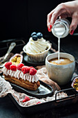 Eclair with berries and cream, and vanilla cupcake, pouring milk into coffee