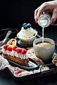 Eclair mit Sahne und Beeren, Vanille-Cupcake und Milch in eine Tasse Kaffee geben