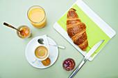 Französisches Frühstück; Kaffee, Croissant, Orangensaft und Marmelade