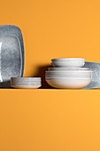 Plates and trays on ledge on yellow wall