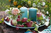 Schale mit Äpfeln, Zieräpfeln, Rose und Kerzen auf Gartenmauer