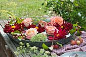 Dahlien und Rosenblüten in Schale mit Wasser