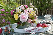 Strauß aus Rosen, Zieräpfeln und Fenchelblüten auf Tablett