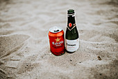 A beer can and prosecco bottle in sand