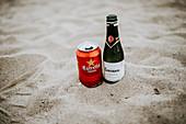 Bierdose und Proseccoflasche im Sand