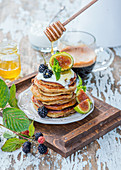 Honey being drizzled over a stack of pancakes with yoghurt, figs and blackberries