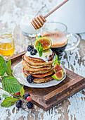 Honig tropft auf Stapel Pancakes mit Joghurt, Feigen und Brombeeren