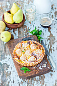 Pear cake with slivered almonds on a wooden board
