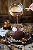Hot chocolate with peanut caramel being poured into a cup