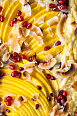 Coconut rice bake with mango, pomegranate seeds and coconut chips