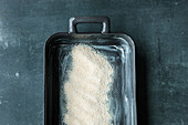 A baking dish being sprinkled with breadcrumbs for a crispy effect