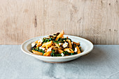Penne pasta with harissa and spinach sauce, feta cheese and black olives