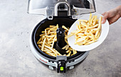 Chips being place in a hot-air fryer