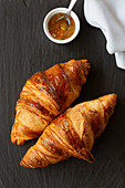 Two classic French flaky croissants with orange confiture