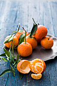 Clementines with leaves on a metal plate