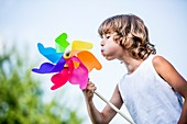 Boy blowing paper windmill