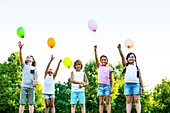 Children standing with balloons