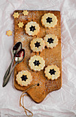 Linzer Plätzchen (nutty shortcrust jam sandwich biscuits with holes on top) on a wooden board