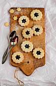 Linzer Plätzchen (nutty shortcrust jam sandwich biscuits with holes on top) on a wooden board