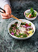 A person eating pho bo (Vietnamese beef and rice noodle soup)