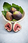 Fresh purple figs in a bowl, one halved