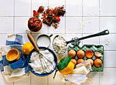 Various baking ingredients on white tiles