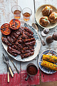 Vegan 'spare ribs' with jacket potatoes, oven-roasted tomatoes and sweetcorn