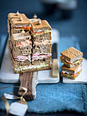 A sandwich cake with smoked salmon, chicken breast and peppers