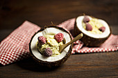 Chia and coconut ice cream with frozen raspberries in coconut bowls