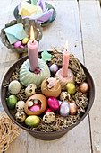 An arrangement of various Easter eggs, quail's eggs and burning candles