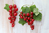 Redcurrants with leaves on a white wooden surface